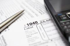 Formas de impuesto, teléfono celular y pluma Fotos de archivo