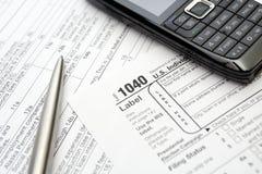 Formas de impuesto, teléfono móvil y pluma Foto de archivo libre de regalías