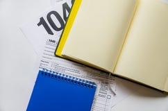Formas de impuesto 1040 y cuadernos en un fondo blanco imagen de archivo