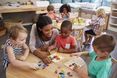 Formas de madeira de And Pupils Using do professor na escola de Montessori imagem de stock royalty free