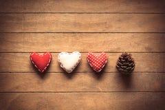 Formas del corazón y cono del pino en backgorund de madera Fotografía de archivo
