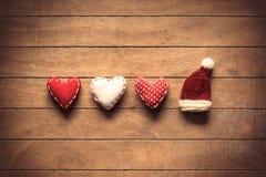 Formas del corazón y sombrero de Santa Claus en fondo de madera Fotos de archivo libres de regalías