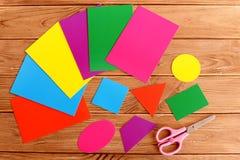 Formas geométricas básicas de papel para la educación de los niños Hojas de la cartulina coloreada, tijeras en una tabla de mader Fotografía de archivo libre de regalías