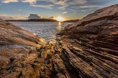 Formas nas rochas pelo mar Luz da noite, oceano, luz morna e sol aproximadamente a ajustar-se no fundo imagens de stock