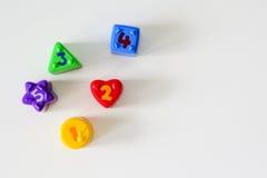 Formas plásticas coloridas con números en un fondo blanco Fotografía de archivo libre de regalías