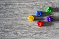 Formas plásticas coloridas con números en un fondo de madera Fotos de archivo libres de regalías