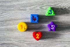 Formas plásticas coloridas con números en un fondo de madera Fotografía de archivo libre de regalías