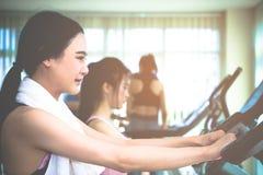 Formation asiatique de fille sur le tapis roulant dans la formation de gymnase de forme physique Photos stock