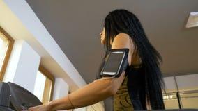 Formation attrayante de femme dans le gymnase avec une courroie de bras de smartphone clips vidéos