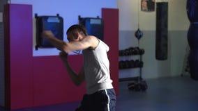 Formation au ralenti et à faible niveau d'éclairement de boxeur d'homme de scène dans le gymnase, combat d'ombre banque de vidéos
