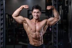 Formation belle de bodybuilder dans les haltères sexy d'ascenseur d'homme de gymnase Photo stock