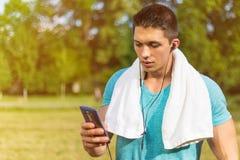 Formation courante de forme physique du smartphone APP de sports de jeune homme extérieure photographie stock