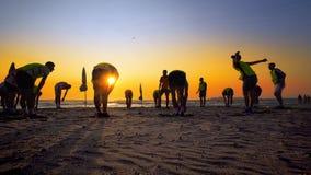 Formation d'équipe de football de jeunes garçons au coucher du soleil sur la plage Photos libres de droits