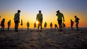 Formation d'équipe de football de jeunes garçons sur la plage de coucher du soleil Images libres de droits