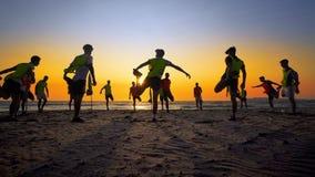 Formation d'équipe de football de jeunes garçons sur la plage de coucher du soleil Image libre de droits