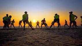 Formation d'équipe de football de jeunes garçons sur la plage de coucher du soleil Photos stock