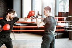 Formation d'homme avec l'entraîneur de boxe sur le ring images stock