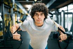 Formation d'homme avec la suspension de TRX au centre de fitness Photo stock