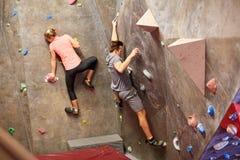 Formation d'homme et de femme au mur s'élevant d'intérieur de gymnase Image stock