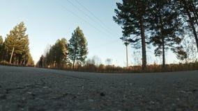 Formation d'un athlète sur les patineurs de rouleau Tour de biathlon sur les skis de rouleau avec des poteaux de ski, dans le cas banque de vidéos