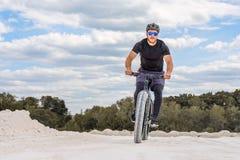 Formation d'un cycliste dans une carrière crayeuse Un homme brutal sur un gros vélo photos libres de droits