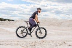 Formation d'un cycliste dans une carrière crayeuse Un homme brutal sur un gros vélo photos stock