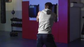 Formation de boxeur d'homme de vue au ralenti et arrière dans le gymnase, combat d'ombre, scène de faible luminosité clips vidéos