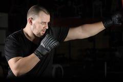 Formation de boxeur sur un sac de sable dans le gymnase images stock