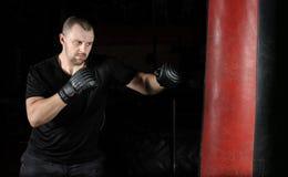 Formation de boxeur sur un sac de sable dans le gymnase image libre de droits