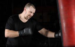 Formation de boxeur sur un sac de sable dans le gymnase photo stock