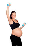 Formation de femme enceinte de brune avec des haltères Image stock