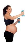 Formation de femme enceinte de brune avec des haltères Photo libre de droits