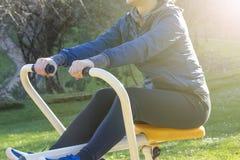Formation de jeune femme avec l'équipement d'exercice en parc public photographie stock libre de droits