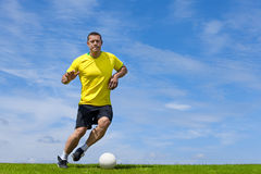 Formation de joueur de football du football sur un lancement d'herbe Photographie stock libre de droits
