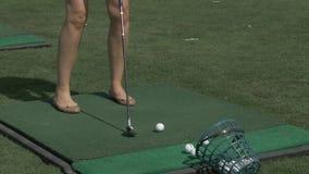 Formation de joueur de golf de jeune femme sur le vert avec le club Coup-de-pied de fille la boule banque de vidéos