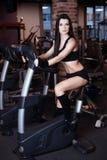 Formation de port de vêtements de sport de jeune femme musculaire sur des vélos d'exercice dans le gymnase Cardio- séance d'entra photo libre de droits