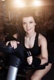Formation de port de vêtements de sport de jeune femme musculaire sur des vélos d'exercice dans le gymnase Cardio- séance d'entra images stock