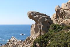 Formation de roche bizarre ressemblant à une main contre le ciel bleu et l'océan, Sardaigne, Italie photographie stock