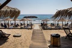 Formation de roche dans l'océan Parapluie tissé, lit plié et dévoilé réglable de chaise de plage faisant face à la mer Chemin en  photo stock