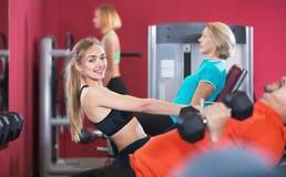 Formation de sourire active d'haltérophilie de personnes dans le club de santé Image stock