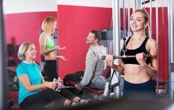 Formation de sourire satisfaisante active d'haltérophilie de personnes dans le club de santé Image stock