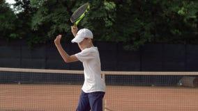 Formation de tennis, technique de service de garçon de l'adolescence utile avec la raquette sans boule sur la cour et prêt de pra banque de vidéos