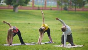 Formation de yoga en parc - les jeunes sportifs exécute l'exercice de flexibilité extérieur banque de vidéos