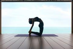 Formation de yoga La femme dans le sport vêtx étirer le corps près de la mer photographie stock