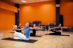 Formation de yoga, séance d'entraînement femelle de groupe dans le gymnase Photos stock