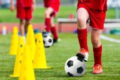 Formation du football du football d'enfants Jeune athlète avec la boule du football image stock
