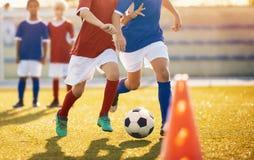 Formation du football Jeunes footballeurs fonctionnant avec la boule Garçons donnant un coup de pied la boule du football Les équ photographie stock