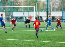 Formation du football pour des enfants Garçons dans les vêtements de sport rouges bleus sur le terrain de football Les jeunes foo photographie stock