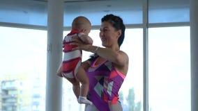 Formation du ` s de maman, elle étire ses bras en lesquels elle tient un petit enfant banque de vidéos