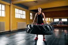 Formation dure intense de crossfit, jeune femme soulevant le grand pneu à image libre de droits